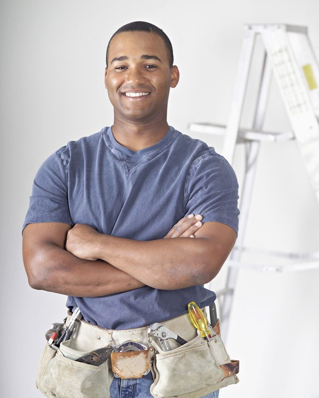 happy contractor wearing tool belt with arms crossed