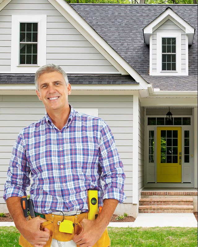 happy contractor standing outside cape style house