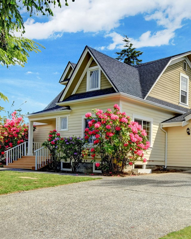 house with yellow siding and pink flowers outside