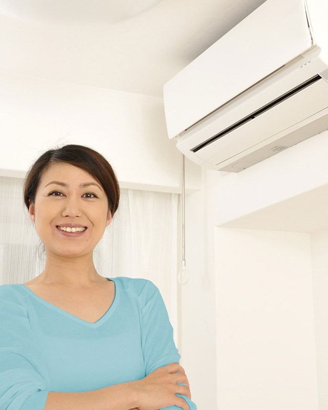 woman standing near interior ac unit