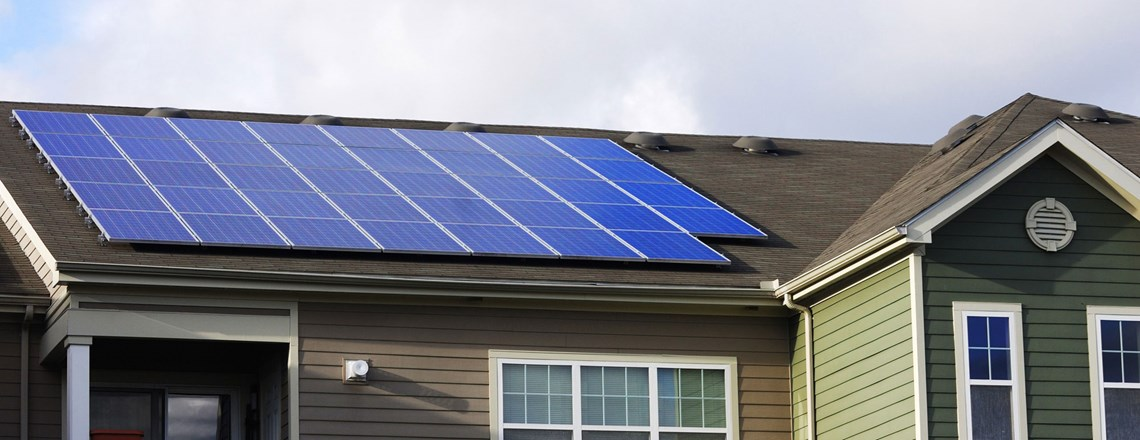 solar panels on roof of green sided house