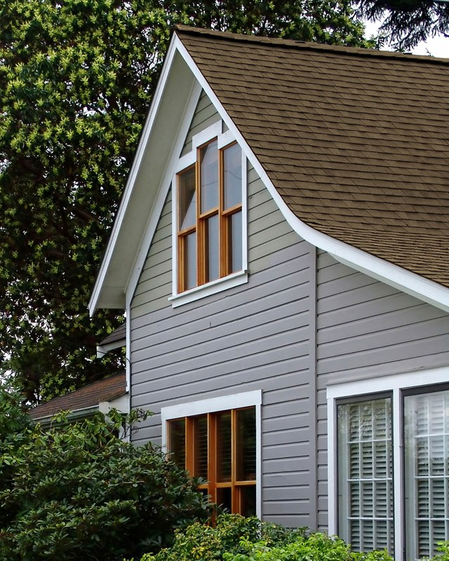 side of gray house with brown shingle roof
