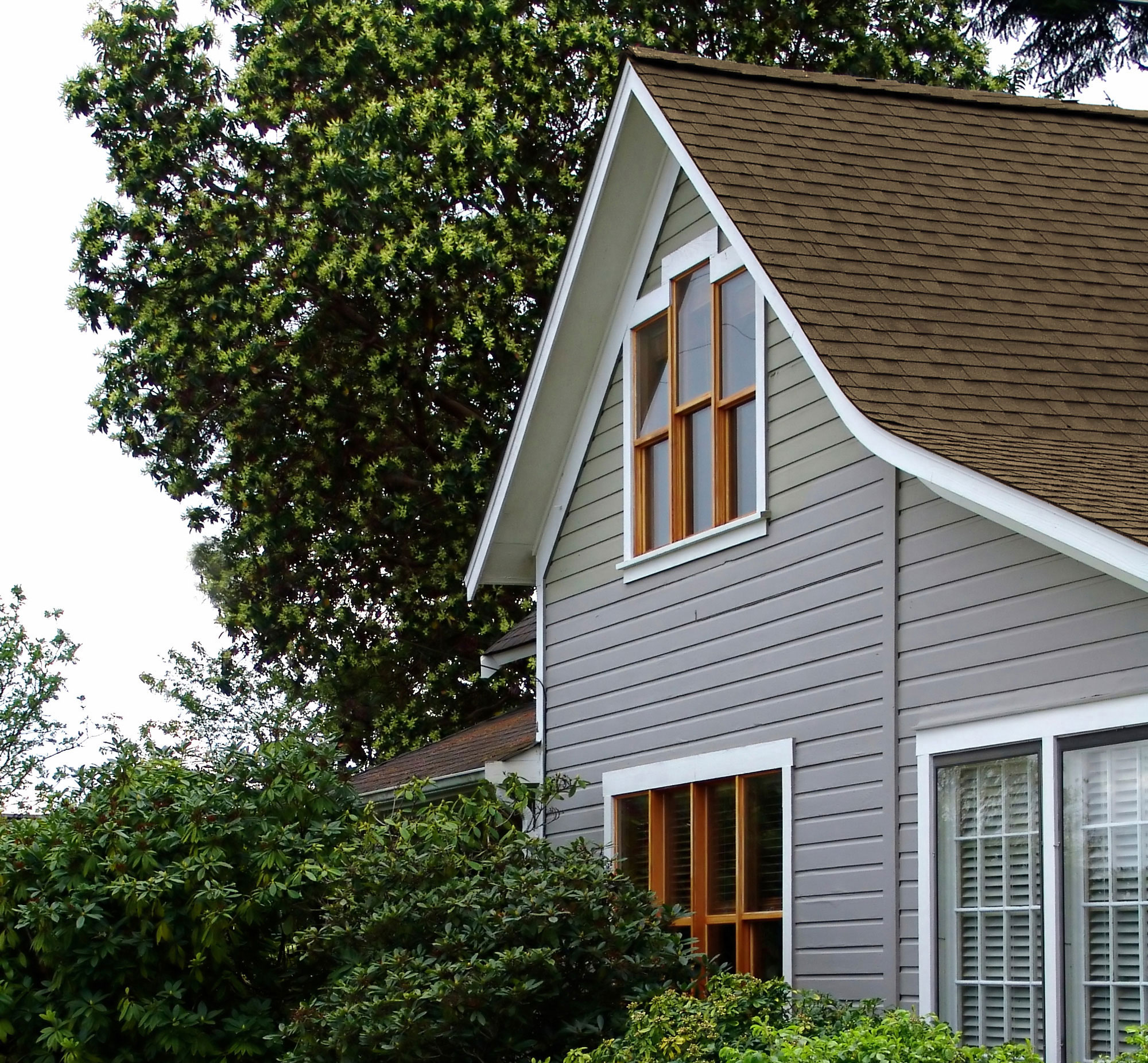 ... Side Of Gray House With Brown Shingle Roof