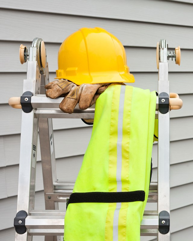 ladder outside house with a hard hat