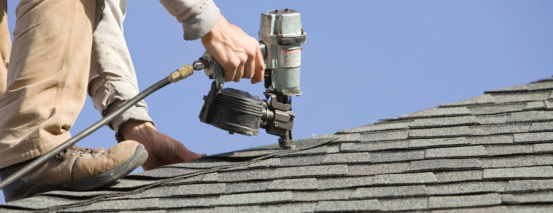 roofer using nail gun on new shingle roof