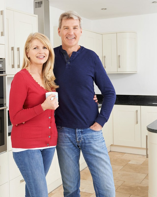 happy older couple standing in kitchen